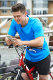 Young Man Using Mobile Phone Whilst Out On Cycle Ride Royalty Free Stock Photography