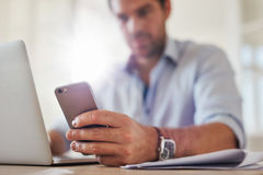 Young man using mobile phone while working on laptop Royalty Free Stock Photo