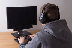 Young man using a computer and listening music Royalty Free Stock Image