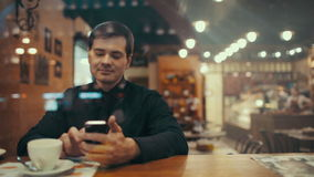 Young man using phone and having coffee in a cafe stock footage