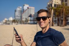 Young man using the phone with headset on the beach. City Skyline In Background. Man using a smartphone on the beach, clear sky and tall buildings as background royalty free stock photography