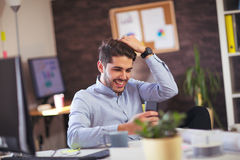 Young man using phone. In office Stock Photo
