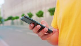 Man Using a Phone Outdoors. A young man using a phone outdoors. Close-up shot royalty free stock photos