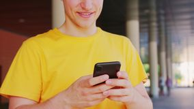 Man Using a Phone Outdoors. A young man using a phone outdoors. Close-up shot royalty free stock photo
