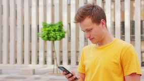 Man Using a Phone Outdoors. A young man using a phone outdoors royalty free stock images