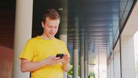 Man Using a Phone Outdoors. A young man using a phone outdoors stock photography