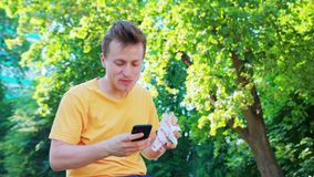 Man Using a Phone Outdoors. A young man using a phone outdoors stock image