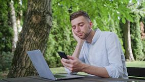 A young man using a phone in the park stock video footage