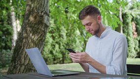 A young man using a phone in the park stock footage