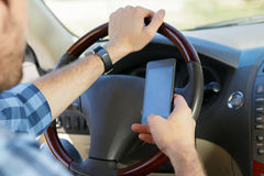 Young man using phone while sitting in the car. Young man using his smartphone while sitting in the car Stock Image