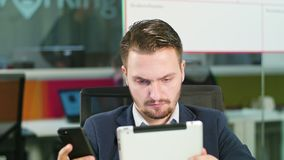 Young man using a phone and a tablet in the office. A young businessman using a smartphone and a tablet in the office. Close-up. Dolly shot. Soft focus stock video