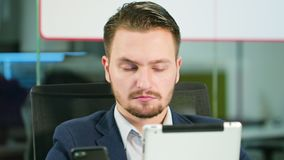 Young man using a phone and a tablet in the office. A young businessman using a smartphone and a tablet in the office. Close-up. Dolly shot. Soft focus stock video footage