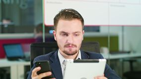Young Man Using a Phone and a Tablet in the Office. A young businessman using a smartphone and a tablet in the office. Close-up. Dolly shot. Soft focus Royalty Free Stock Image