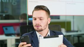 Young Man Using a Phone and a Tablet in the Office. A young businessman using a smartphone and a tablet in the office. Close-up. Dolly shot. Soft focus Stock Image