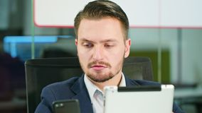 Young Man Using a Phone and a Tablet in the Office. A young businessman using a smartphone and a tablet in the office. Close-up. Dolly shot. Soft focus Stock Images