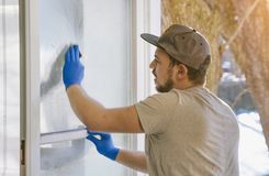 Young man is using a rag and squeegee while cleaning windows. stock photography