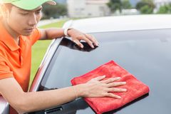 Free Young Man Using Red Microfiber Cloth Cleaning Body Of New Silver Royalty Free Stock Images - 100485619