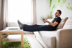 Young man using remote control while sitting on couch in living room Stock Images