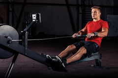 Young man using rowing machine in the gym royalty free stock photo