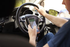 Young Man Using Satellite Navigation on Phone Whilst Driving Royalty Free Stock Photo