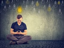 Man using smart phone with bright light bulb above head stock images