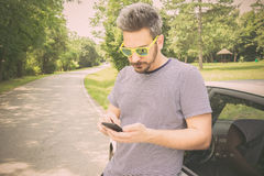 Young man using smart phone next to the car. Tourist guy standing next to car and looking at smart phone. Driver using road map navigation app or calling road Royalty Free Stock Photos