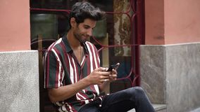 Young man using smart phone sitting on urban step. stock footage