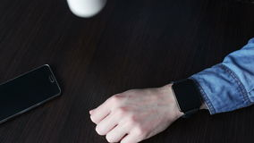 Young man using a smart watch. Young man in a stylish jeans shirt with black smart clock holding white cup of coffee and lies next to a smartphone looking at the stock video footage