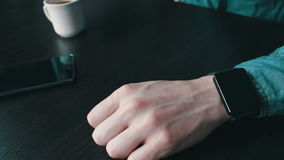 Young man using a smart watch. Young man in a stylish jeans shirt with black smart clock lies next to a smartphone looking at the clock face close up view stock video footage