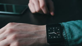 Young man using a smart watch. Young man in a stylish jeans shirt with black smart clock lies next to a smartphone looking at the clock face close up view stock footage