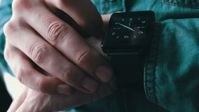 Young man using a smart watch. Young man in a stylish jeans shirt and black smart clock and looking at the clock face stock video footage