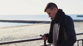 Young man using a smartphone on the autumn beach. Slow motion stock video footage