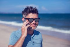 Young man using smartphone on the beach. A Young man using smartphone on the beach Royalty Free Stock Photos
