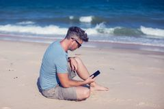Young man using smartphone on the beach. A Young man using smartphone on the beach Royalty Free Stock Photography