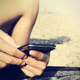 Young man using a smartphone on the beach, filtered Stock Photography
