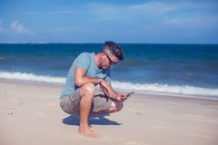 Young man using smartphone on the beach. A Young man using smartphone on the beach Stock Photography