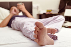 Young man using a smartphone in bed Stock Images