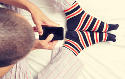 Young man using a smartphone in bed Stock Photography