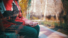 Young man using a smartphone on a bench in the city park. A man holds a Mobile Phone in his hands and controls his finger gestures and looks at social networks stock video