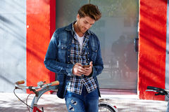 Young man using smartphone in a bicycle Royalty Free Stock Images