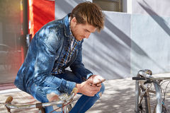 Young man using smartphone in a bicycle Stock Image