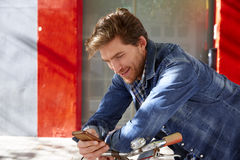 Young man using smartphone in a bicycle Stock Photo