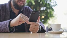 A Young Man Using a Smartphone in the Cafe. Close-up shot. Soft focus stock video