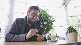 A Young Man Using a Smartphone in the Cafe. Medium shot stock footage