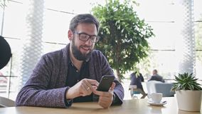 A Young Man Using a Smartphone in the Cafe. Medium shot stock video footage