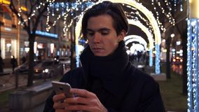 Man using smartphone on city street at night. Lights decorations at background. Young man using smartphone on city street at night. Car traffic, lot of people stock footage