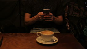 Young man using smartphone drinking coffee in cafe. Young man using cellphone drinking coffee in cafe stock video