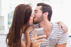 Young man using smartphone while girlfriend kisses him Royalty Free Stock Photo