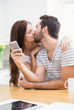 Young man using smartphone while girlfriend kisses him Royalty Free Stock Image