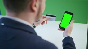A Young Man Using a Smartphone with a Green Screen. And holding a credit card indoors. Close-up shot. Soft focus stock footage